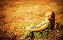 Romantic woman on golden field. Romantic woman wearing long elegant dress sitting on golden dry field, autumn season, relaxation in countryside, enjoying nature Stock Photography