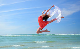 Romantic woman jumping on the beach Stock Photo