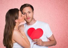 Romantic woman kissing on the cheek of man holding a heart shape. Against pink background Stock Photos