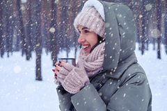 Romantic woman in knitted cap and scarf enjoying a cup of hot te Royalty Free Stock Images