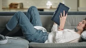 Romantic woman lying on coach with photo album. Smiling girl looking photobook. At living room. Relaxed woman dreaming on sofa at open kitchen stock video