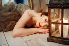 Romantic woman lying on a floor near retro lantern with candles Stock Photos