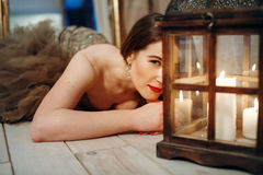 Romantic woman lying on a floor near retro lantern with candles Royalty Free Stock Photos