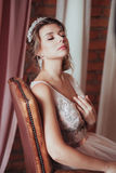 Romantic Woman in pink bridal dress sitting on brown armchair. Face with closed eyes lifted up. Indoor, interior, studio.  Royalty Free Stock Image