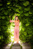 Romantic woman posing at floral arch at garden Royalty Free Stock Photo
