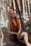 Romantic woman with red hair lying in the grass in the woods. A girl in a light black dress sleeps and dreams in a magical forest.