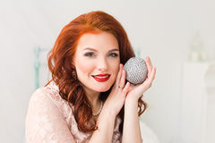 Romantic woman with red lips and saucy Christmas silver ball Stock Photo