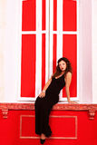 Romantic woman in red vintage room sitting on sill fashion glamo Royalty Free Stock Photo