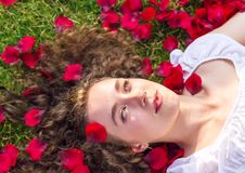 Romantic woman in rose petals royalty free stock photo