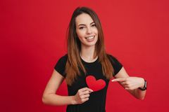 Romantic woman 20s with long brown hair smiling and gesturing fi. Nger at paper heart isolated over red background Royalty Free Stock Image