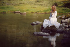 Romantic woman seated on lake rocks. Lone romantic woman seated on mountain lake rocks Royalty Free Stock Photography