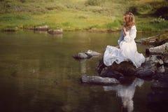 Romantic Woman Seated On Lake Rocks Royalty Free Stock Photography