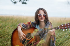 Romantic woman with short straight dark hair wearing cape and sunglasses while resting at green field enjoying beautiful landscape Royalty Free Stock Photo