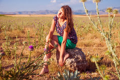 Romantic woman sitting in the field, autumn season. Romantic woman sitting on the stone in the field, autumn season Royalty Free Stock Photos