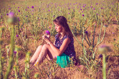 Romantic woman sitting in the field with a flower. Romantic woman sitting on the stone in the field, autumn season Stock Photography
