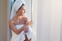 Romantic woman sitting before window and admiring sunrise or sunset with towel on her head body after bath. Stock Photos