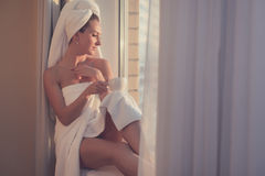 Romantic woman sitting before window and admiring sunrise or sunset with towel on her head body after bath. Stock Photography
