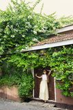 Bush blooming bougainvillea. Romantic woman standing near old doors under a bush of blossoming bougainvillea Stock Photo