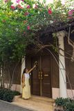 Woman knocks at the door. Romantic woman standing near old doors under a bush of blossoming bougainvillea Stock Images