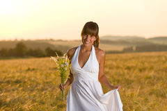 Romantic woman in sunset corn field wear dress. Romantic brunette woman in sunset corn field wear white dress, holding bouquet of flowers Royalty Free Stock Photo