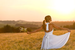 Romantic woman in sunset corn field wear dress. Romantic brunette woman in sunset corn field wear white dress, holding bouquet of flowers Royalty Free Stock Images