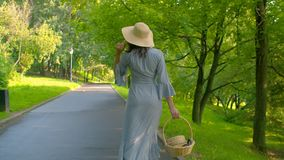 Romantic woman walking in the park. Romantic woman with basket in her hand walking in the park. Rear view, slow motion stock footage