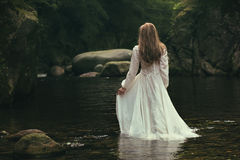 Romantic woman walks into a stream Stock Image