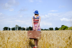 Romantic woman wearing hat with suitcase walking. Elegant female wearing hat with suitcase walking away through wheat field. Backview of girl in striped dress Stock Photo