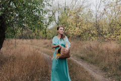 Romantic woman wearing long elegant dress standing on the field, autumn season, relaxation in countryside, enjoying nature, pleasu Stock Images