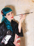 Romantic women with a cigarette holder. Portrait of romantic woman with a blue hair with a cigarette holder Stock Photos