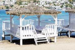Romantic wooden  lounge bungalows on the beach.Bodrum,Turkey. Romantic wooden  lounge house at the  beach with stairs leading to the water Royalty Free Stock Photography