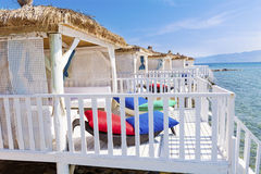Romantic wooden  lounge bungalows with rattan sunbeds on the sea. Romantic wooden  lounge house at the  beach with stairs leading to the water Royalty Free Stock Photo