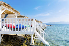 Romantic wooden  lounge bungalows with rattan sunbeds on the sea Royalty Free Stock Images
