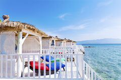 Romantic wooden  lounge bungalows with rattan sunbeds on the sea. Romantic wooden  lounge house at the  beach with stairs leading to the water Royalty Free Stock Images
