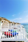 Romantic wooden  lounge bungalows with rattan sunbeds on the sea. Romantic wooden  lounge house at the  beach with stairs leading to the water Royalty Free Stock Image