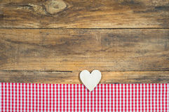 Romantic wooden love heart on red checkered fabric and rustic wood background. Wooden heart with red checkered fabric on rustic wooden background with copy Royalty Free Stock Image