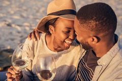 Romantic young African couple drinking wine together at the beach. Laughing young African couple sitting together on a sandy beach at sunset enjoying a glass of stock photos