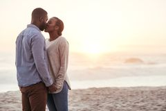 Romantic young African couple kissing on a beach at sunset. Romantic young African couple standing together on a sandy beach at sunset holding hands and kissing Royalty Free Stock Photo