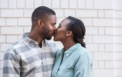 Romantic young African couple kissing each other in the city. Romantic young African couple kissing each other while standing together in front of a brick wall Stock Images