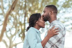 Romantic young African man kissing his girlfriend`s forehead outdoors. Romantic young African men kissing his girlfriend on the forehead while standing together stock photo