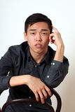 Romantic young Asian man sitting on a chair Royalty Free Stock Photography