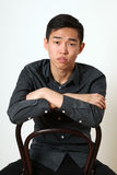 Romantic young Asian man sitting on a chair Stock Photos