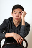 Romantic young Asian man sitting on a chair Royalty Free Stock Photos