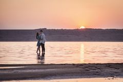 Romantic young beautiful couple in the background of the sun. stock photo