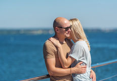 Romantic young beautiful couple standing on pier of river. royalty free stock image