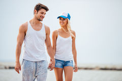 Romantic young beautiful couple walking on the beach holding hands Royalty Free Stock Photography