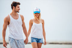 Romantic young beautiful couple walking on the beach holding hands Royalty Free Stock Images