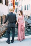 Romantic young beautiful couple walking in venetian canal. Italy, Europe. royalty free stock photos