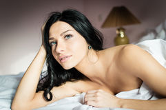 Romantic young beautiful soft woman in bed looking up Stock Image