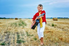 Romantic young boy with guitar in the field. Romantic boy with a guitar in the field . fashionable little musician in nature . children`s music education stock photography